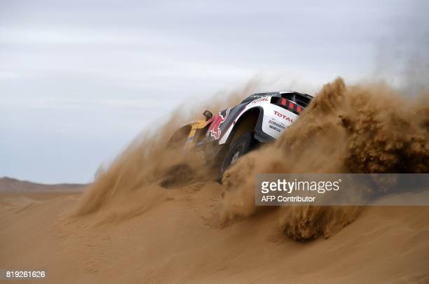 Peugeot's driver Stephane Peterhansel and his codriver Jean Paul Cottret of France ride over a sand dune as they compete during the Stage 12 of the...