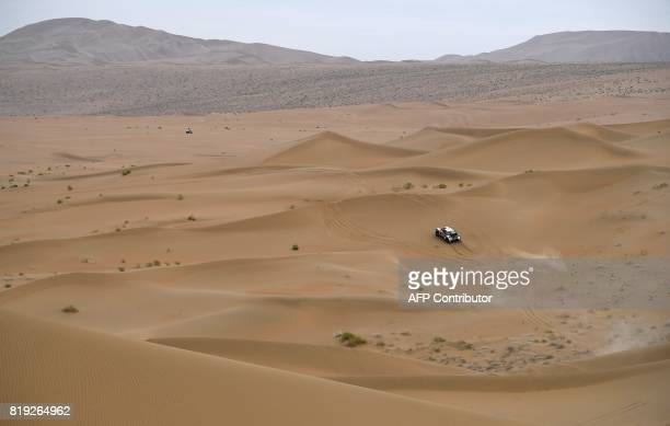 Peugeot's driver Stephane Peterhansel and his codriver Jean Paul Cottret of France ride over sand dunes as they compete during the Stage 12 of the...