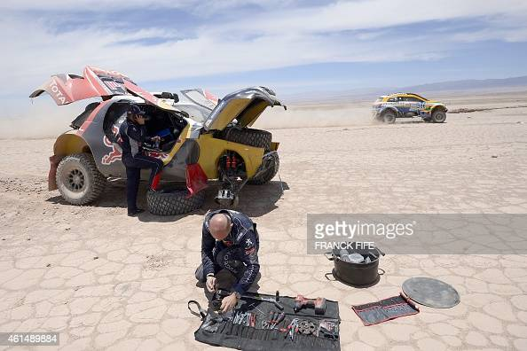 Peugeot's driver Stephane Peterhansel of France and codriver Jean Paul Cottret Karginov take care of their car during the Stage 9 of the Dakar 2015...