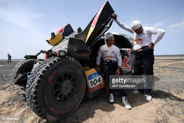 Peugeot's French driver Sebastien Loeb and codriver Daniel Elena of France check their vehicle during the Stage 9 of the Silk Way 2017 between Urumqi...