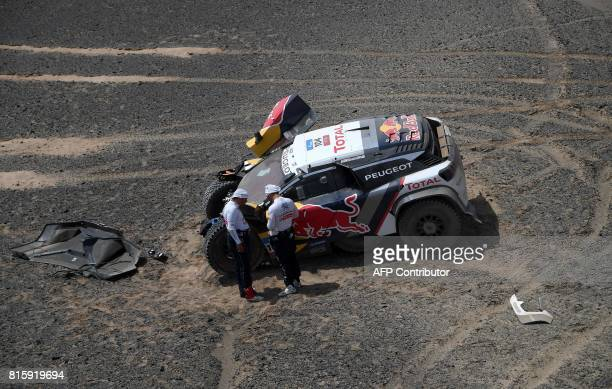 Peugeot's French driver Sebastien Loeb and French codriver Daniel Elena examine their vehicle after a mechanical problem during the Stage 9 of the...