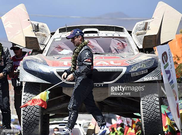 TOPSHOT Peugeot's French driver Sebastien Loeb walks in front of a car on the podium at the end of the Stage 5 of the Dakar 2016 between Jujuy in...