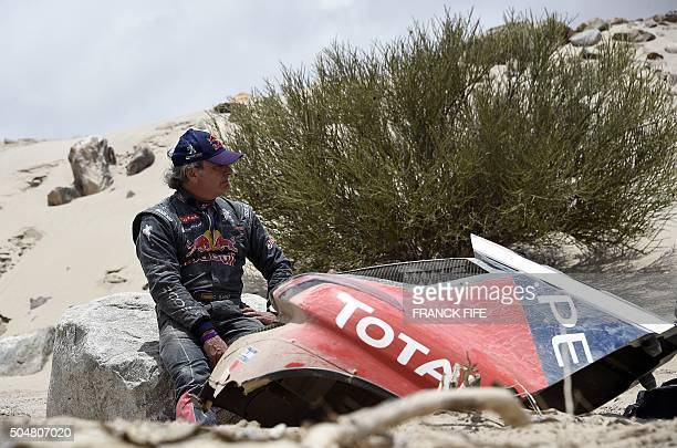 Peugeot's Spanish drivers Carlos Sainz gestures next to his car after a mechanical failure during the Stage 10 of the Dakar 2016 between Belen and La...