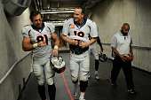 Peyton Manning of the Denver Broncos and Owen Daniels walk to the locker room after the second half of the Broncos' 2412 win at Ford Field The...