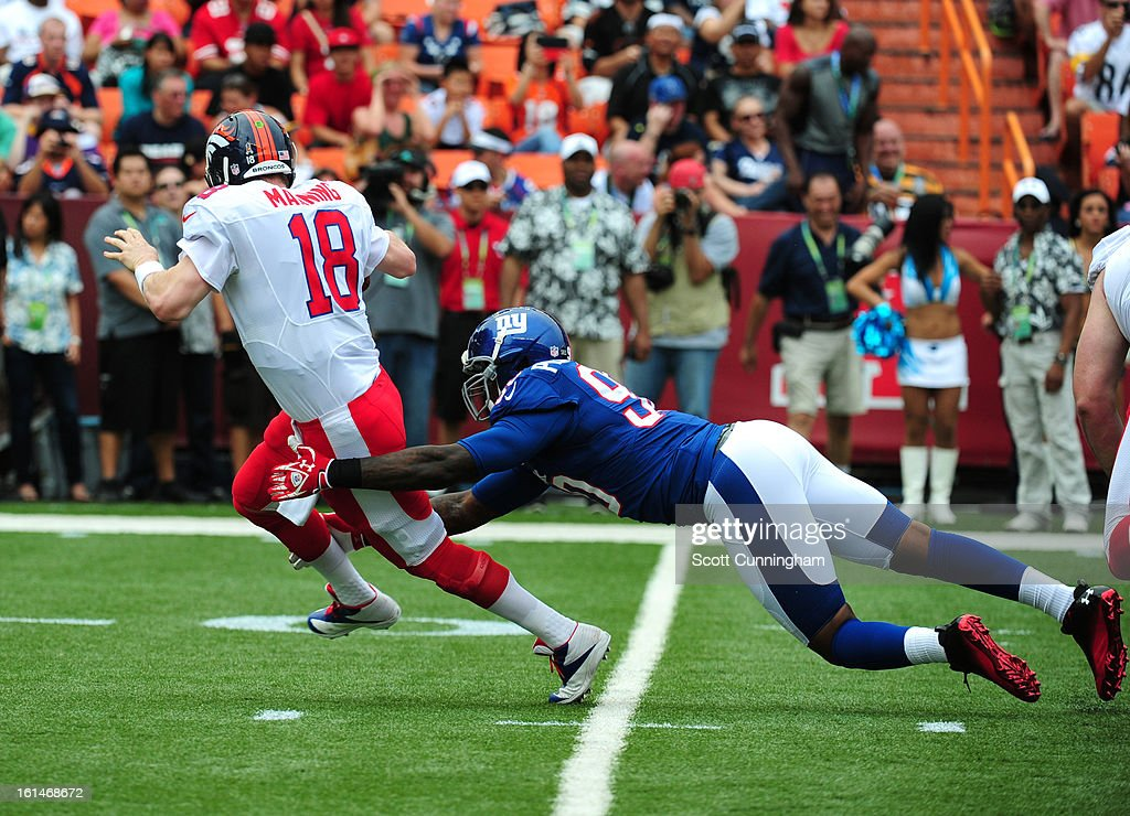 Peyton Manning #18 of the Denver Broncos and the AFC is sacked by Jason Pierre-Paul #90 of the NFC team during the 2013 Pro Bowl at Aloha Stadium on January 27, 2013 in Honolulu, Hawaii.