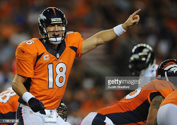 Peyton Manning of the Denver Broncos calls out to his teammates behind center against the Baltimore Ravens in the first half during the game at...