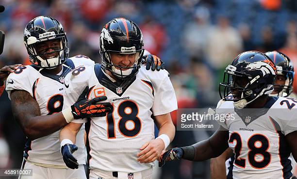 Peyton Manning of the Denver Broncos celebrates with Demaryius Thomas and Montee Ball after Manning set the NFL record for touchdown passes in a...