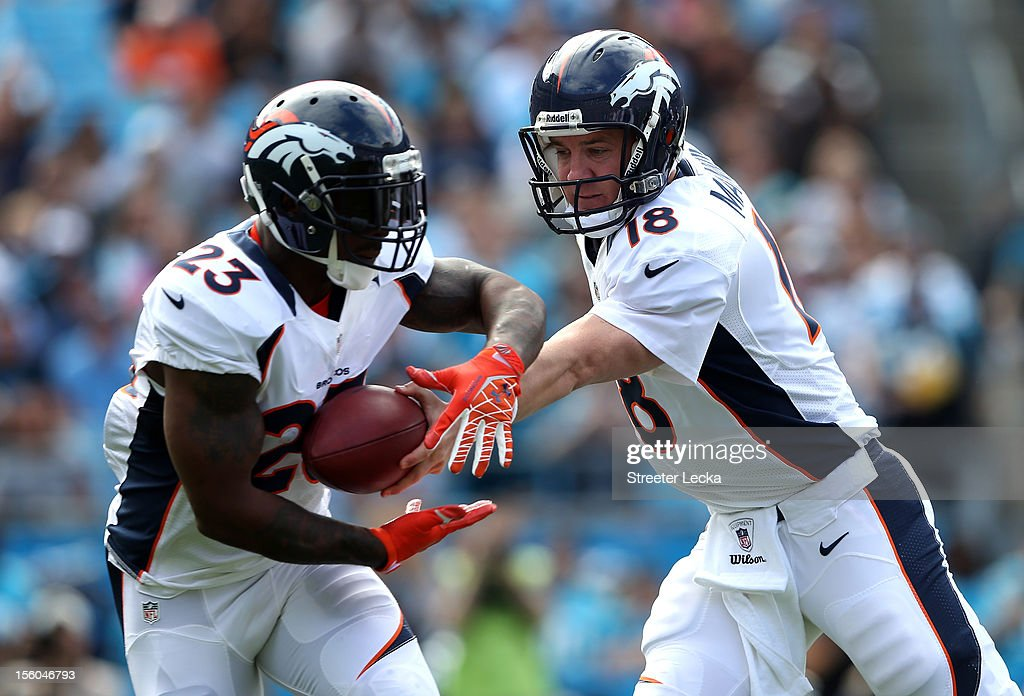 Peyton Manning #18 of the Denver Broncos hands the ball off to teammate Willis McGahee #23 during their game at Bank of America Stadium on November 11, 2012 in Charlotte, North Carolina.
