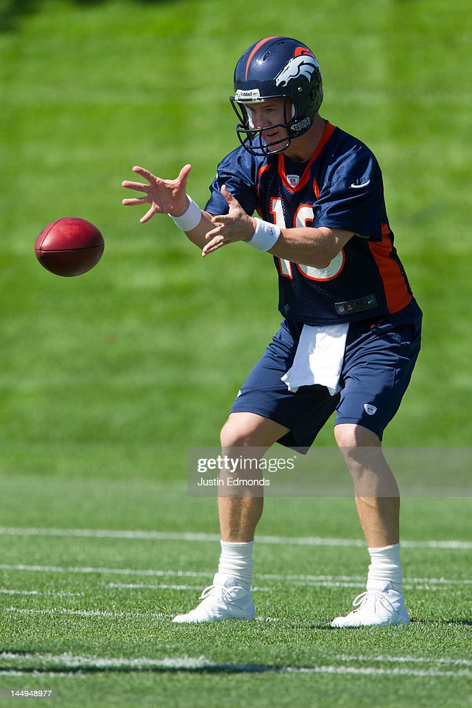 Peyton Manning #18 of the Denver Broncos receives the ball during organized team activities at Dove Valley on May 21, 2012 in Englewood, Colorado.