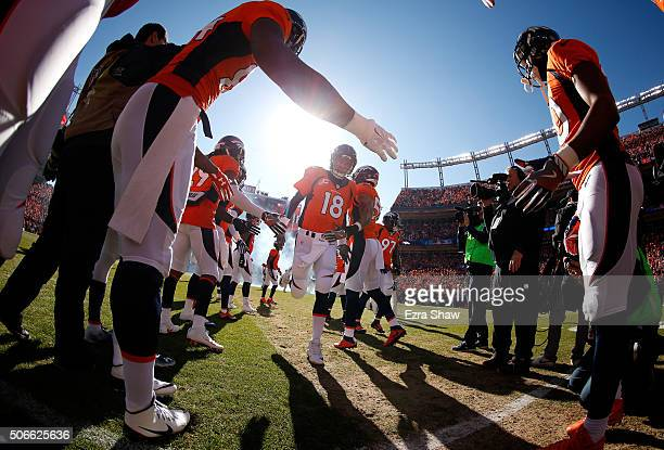 Peyton Manning of the Denver Broncos runs on to the field with teammates before the AFC Championship game against the New England Patriots at Sports...