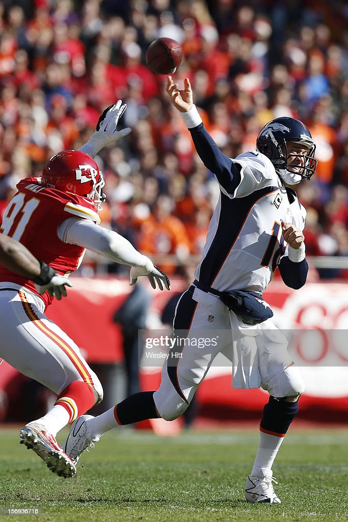 Peyton Manning #18 of the Denver Broncos throws a pass under pressure from Tamba Hali #91of the Kansas City Chiefs at Arrownhead Stadium on November 25, 2012 in Kansas City, Missouri.