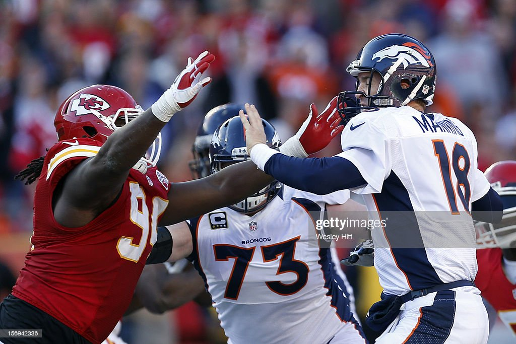 Peyton Manning #18 of the Denver Broncos tries to throw a pass under pressure from Tyson Jackson #94 of the Kansas City Chiefs at Arrowhead Stadium on November 25, 2012 in Kansas City, Missouri. The Broncos defeated the Chiefs 17-9.