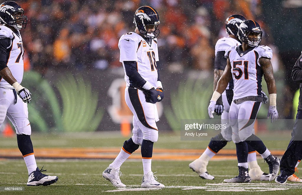 Peyton Manning #18 of the Denver Broncos walks off of the field after throwing an interception to Dre Kirkpatrick #27 of the Cincinnati Bengals during the fourth quarter at Paul Brown Stadium on December 22, 2014 in Cincinnati, Ohio. Cincinnati defeated Denver 37-28.
