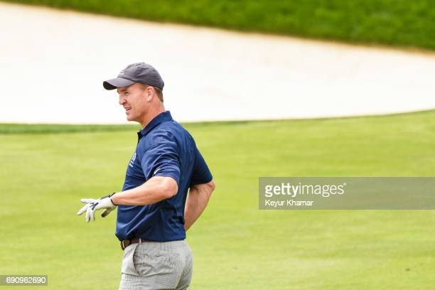 Peyton Manning reacts to the distance of his drive on the 17th hole in a proam round during practice for the Memorial Tournament presented by...