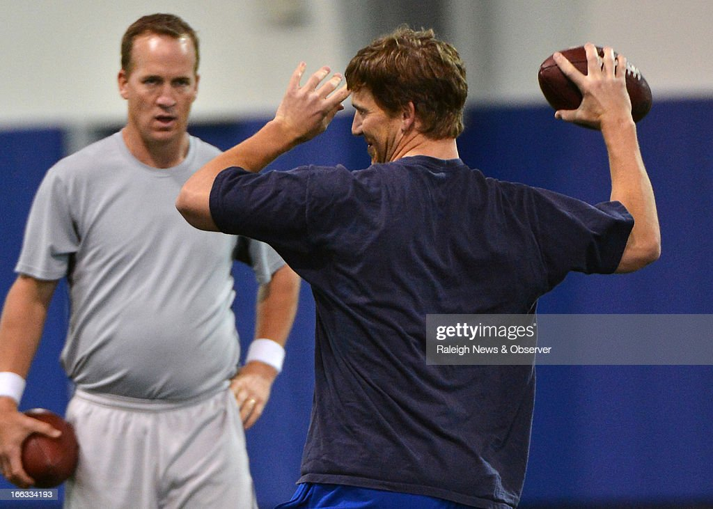 Peyton Manning watches his brother Eli throw a pass during a workout at Duke's Pascal Field House in Durham, North Carolina, Thursday, April 11, 2013.