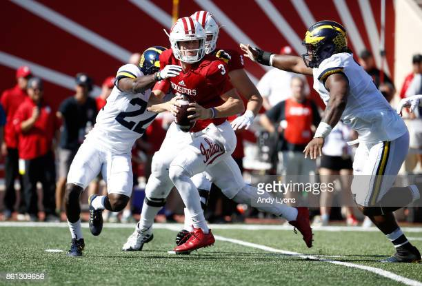 Peyton Ramsey of the Indiana Hoosiers tries to avoid the rush of David Long and Brad Robbins of the Michigan Wolverines during the game at Memorial...