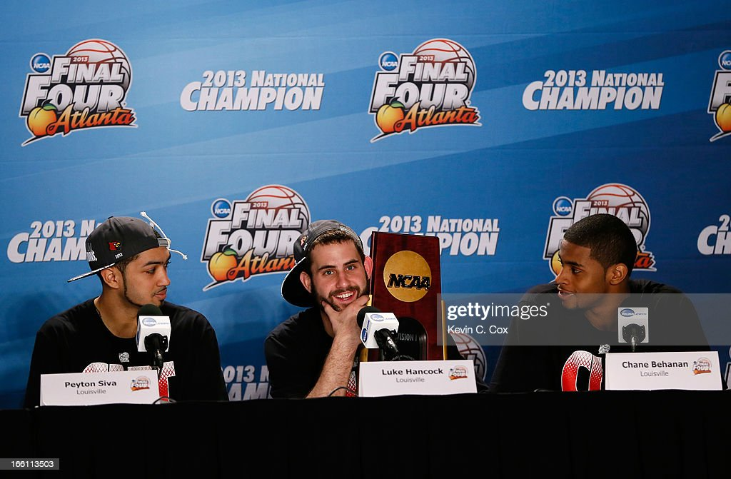 Peyton Siva #3, Luke Hancock #11 and Chane Behanan #21 of the Louisville Cardinals celebrate with the trophy as they answer questions from the media at their post game press conference after they won 82-76 against the Michigan Wolverines during the 2013 NCAA Men's Final Four Championship at the Georgia Dome on April 8, 2013 in Atlanta, Georgia.