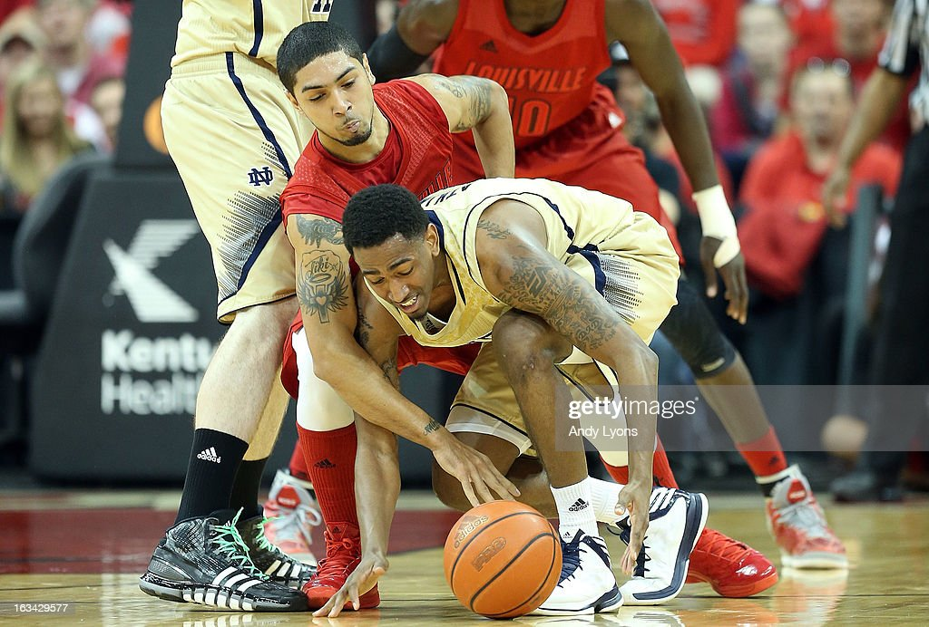 Peyton Siva #3 of the Louisville Cardinals and Eric Atkins #0 of the Notre Dame Fighting Irish battle for a loose ball during the game at KFC YUM! Center on March 9, 2013 in Louisville, Kentucky.