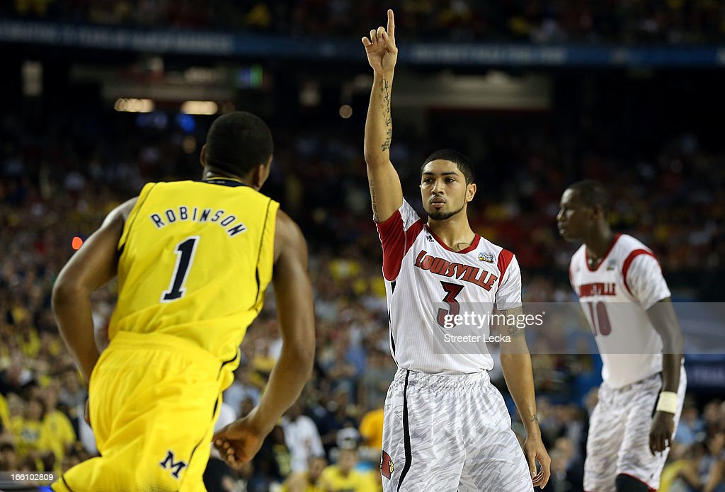 <a gi-track='captionPersonalityLinkClicked' href=/galleries/search?phrase=Peyton+Siva&family=editorial&specificpeople=5792001 ng-click='$event.stopPropagation()'>Peyton Siva</a> #3 of the Louisville Cardinals celebrates in the final second against <a gi-track='captionPersonalityLinkClicked' href=/galleries/search?phrase=Glenn+Robinson+III&family=editorial&specificpeople=9920511 ng-click='$event.stopPropagation()'>Glenn Robinson III</a> #1 of the Michigan Wolverines during the 2013 NCAA Men's Final Four Championship at the Georgia Dome on April 8, 2013 in Atlanta, Georgia.