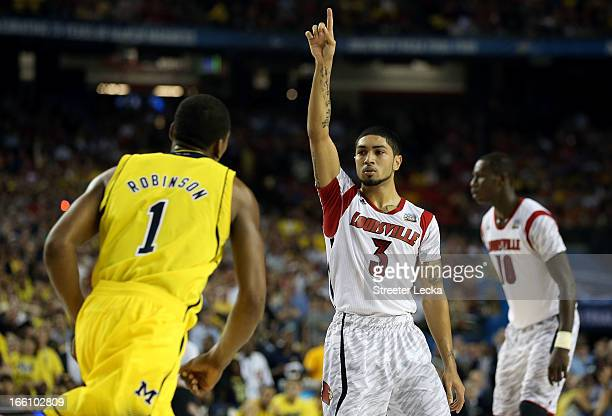Peyton Siva of the Louisville Cardinals celebrates in the final second against Glenn Robinson III of the Michigan Wolverines during the 2013 NCAA...