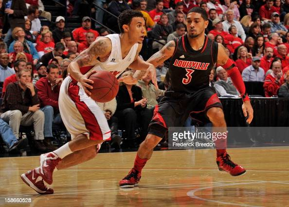 Peyton Siva of the Louisville Cardinals defends Brandon Harris of the Western Kentucky Hilltoppers at Bridgestone Arena on December 22 2012 in...