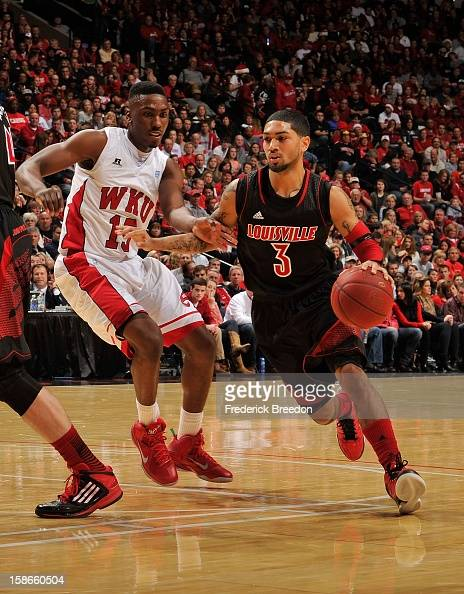 Peyton Siva of the Louisville Cardinals dribbles the ball past O'Karo Akamune of the Western Kentucky Hilltoppers at Bridgestone Arena on December 22...