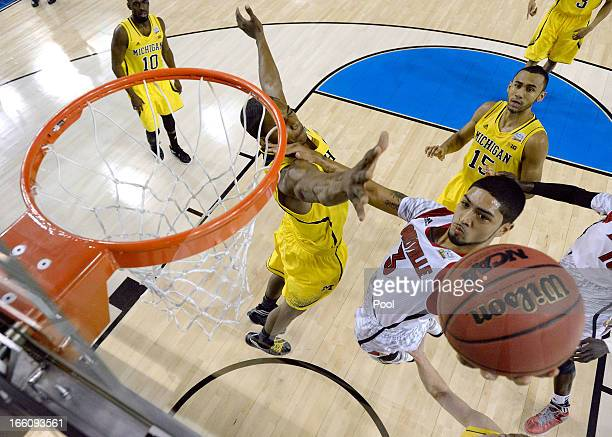 Peyton Siva of the Louisville Cardinals drives for a shot attempt in the first half against Glenn Robinson III of the Michigan Wolverines during the...