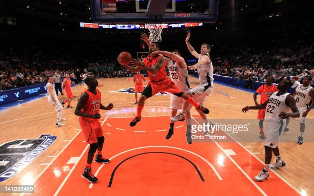 Peyton Siva of the Louisville Cardinals drives to the basket against Jack Cooley and Scott Martin of the Notre Dame Fighting Irish during the...