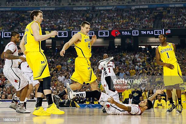 Peyton Siva of the Louisville Cardinals falls to the court as he loses the ball against Nik Stauskas Mitch McGary and Glenn Robinson III of the...