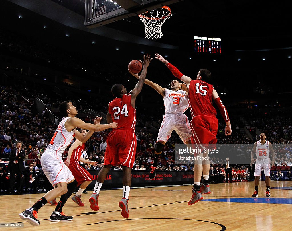 Peyton Siva #3 of the Louisville Cardinals goes up for a shot between De'Mon Brooks #24 and Jake Cohen #15 of the Davidson Wildcats in the second half in the second round of the 2012 NCAA men's basketball tournament at Rose Garden Arena on March 15, 2012 in Portland, Oregon.