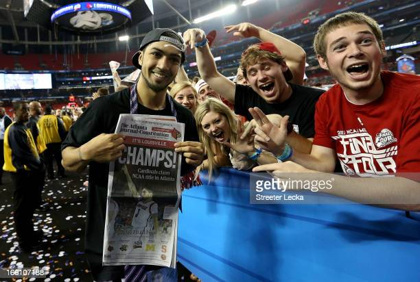 Peyton Siva of the Louisville Cardinals holds up a newspaper which reads 'Champs' as he celebrates with fans after Louisville won 8276 against the...