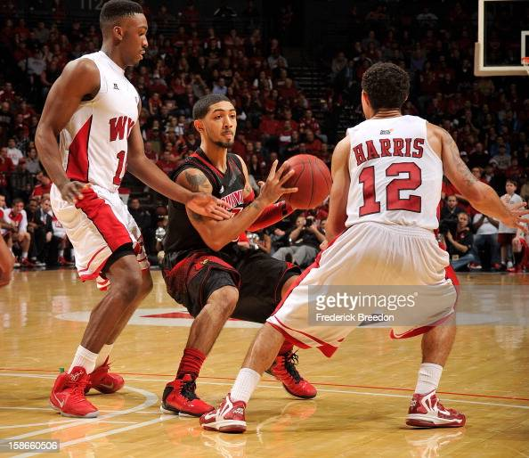Peyton Siva of the Louisville Cardinals looks to pass agasint Brandon Harris of the Western Kentucky Hilltoppers at Bridgestone Arena on December 22...