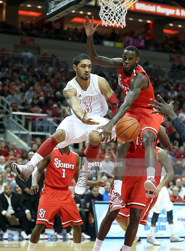 Peyton Siva #3 of the Louisville Cardinals passes the ball while defended by JaKarr Sampson #14 of the St. John's Red Storm during the game at KFC YUM! Center on February 14, 2013 in Louisville, Kentucky.