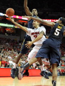 Peyton Siva of the Louisville Cardinals shoots the game winning shot while defended by John Flowers and Kevin Jones of the West Virginia Mountaineers...