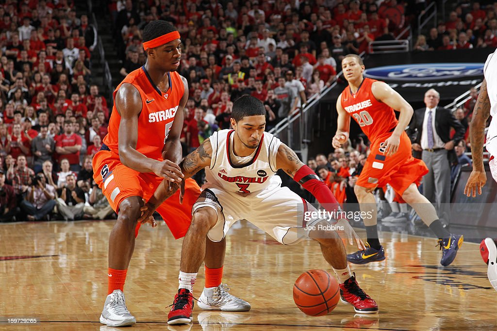 Peyton Siva #3 of the Louisville Cardinals takes the ball away from C.J. Fair #5 of the Syracuse Orange during the game at KFC Yum! Center on January 19, 2013 in Louisville, Kentucky.