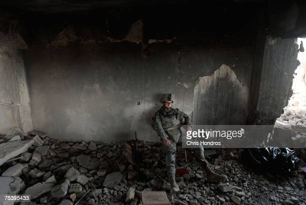 Pft Daniel Sims of Clemson South Carolina of the 1st Battalion 5th Cavalry Regiment of the US Army sits during watch duties in a partially destroyed...