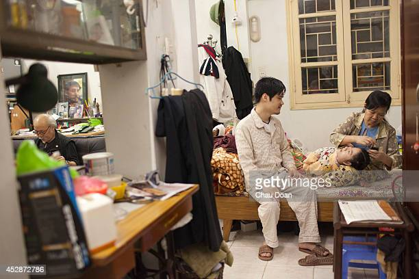 Pham Thi Duc 58 dresses her daughter after a bath at their apartment in Hanoi while talking with her son Nguyen Thanh Tung Duc is the wife of a war...