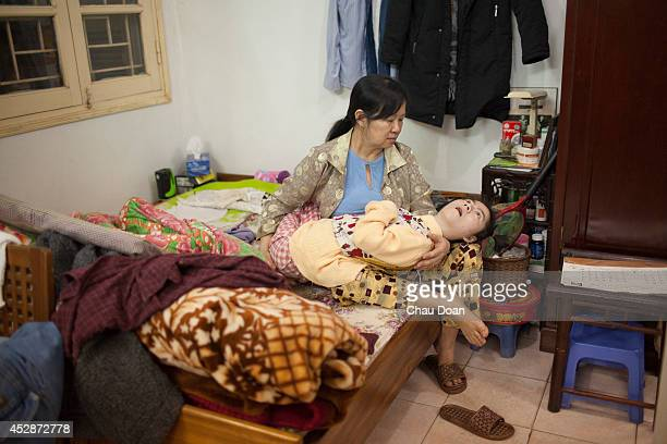 Pham Thi Duc 58 holds her daughter after giving her a bath in their apartment in Hanoi Duc is the wife of a war veteran Nguyen Thanh Son 62 In 1972...