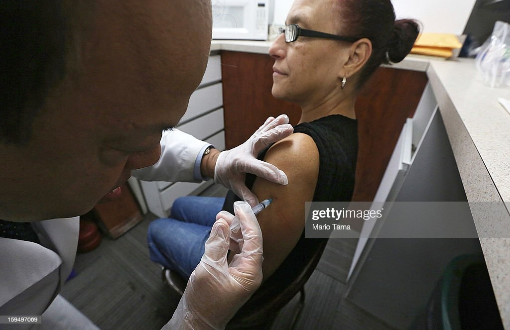 Phamacist Prakash Deshpande injects Judith Echevarria with influenza vaccine at a Manhattan pharmacy on January 14, 2013 in New York City. The state of New York has declared a public health emergency in a flu epidemic of more than 19,000 confirmed cases in the state.