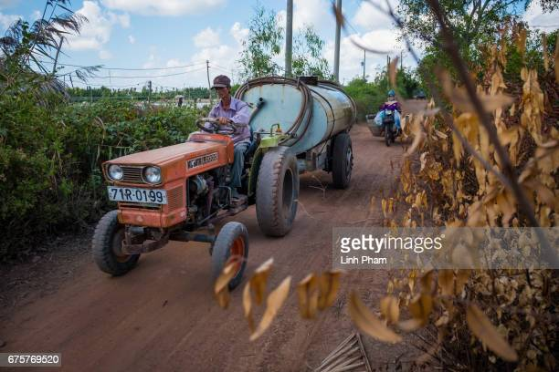 Phan Van Thu 52 A water truck driver delivers fresh water he bought from nearby village to his clients house in Thua Duc Village Binh Dai District...