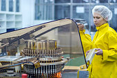 Pharmaceutical worker wearing protective work wear. Female worker preparing machine for work.