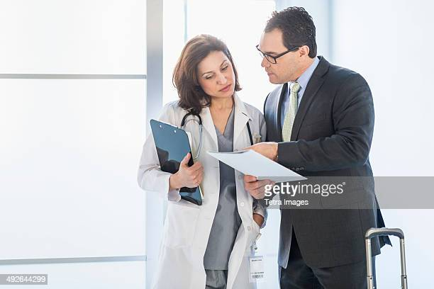 Pharmaceutical representative talking to female doctor, Jersey City, New Jersey, USA