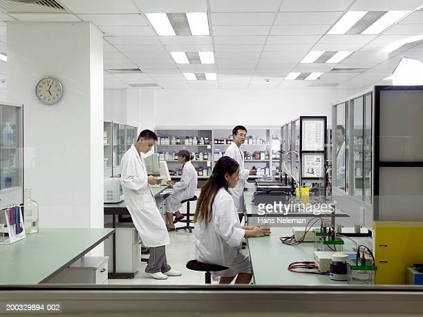 Pharmaceutical researchers working in laboratory, side view