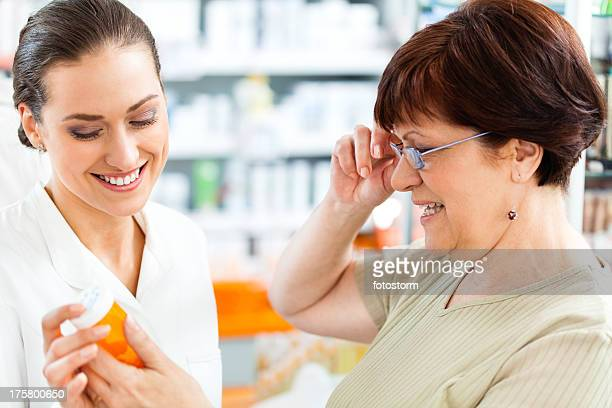 Pharmacist and customer looking at instructions on pill bottle