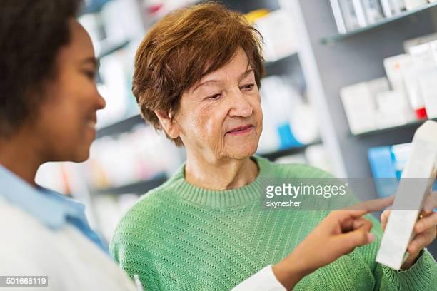 Pharmacist assisting senior woman.