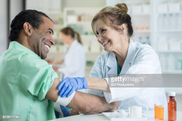 Pharmacist bandages customer's arm after flu shot