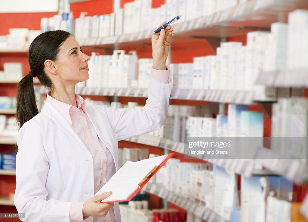 Pharmacist browsing medicine on shelves : Stock Photo