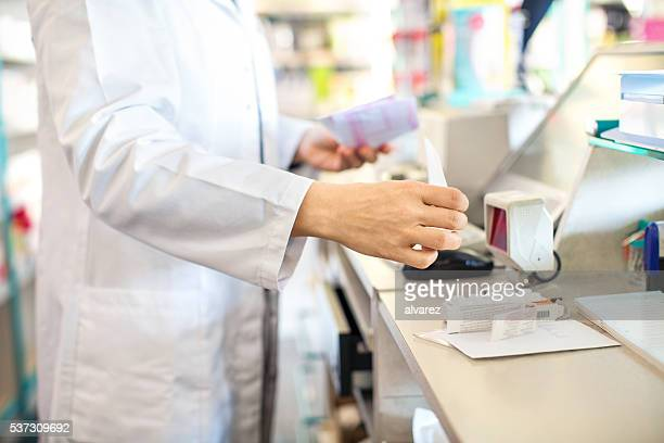 Pharmacist checking out customer's medication prescription