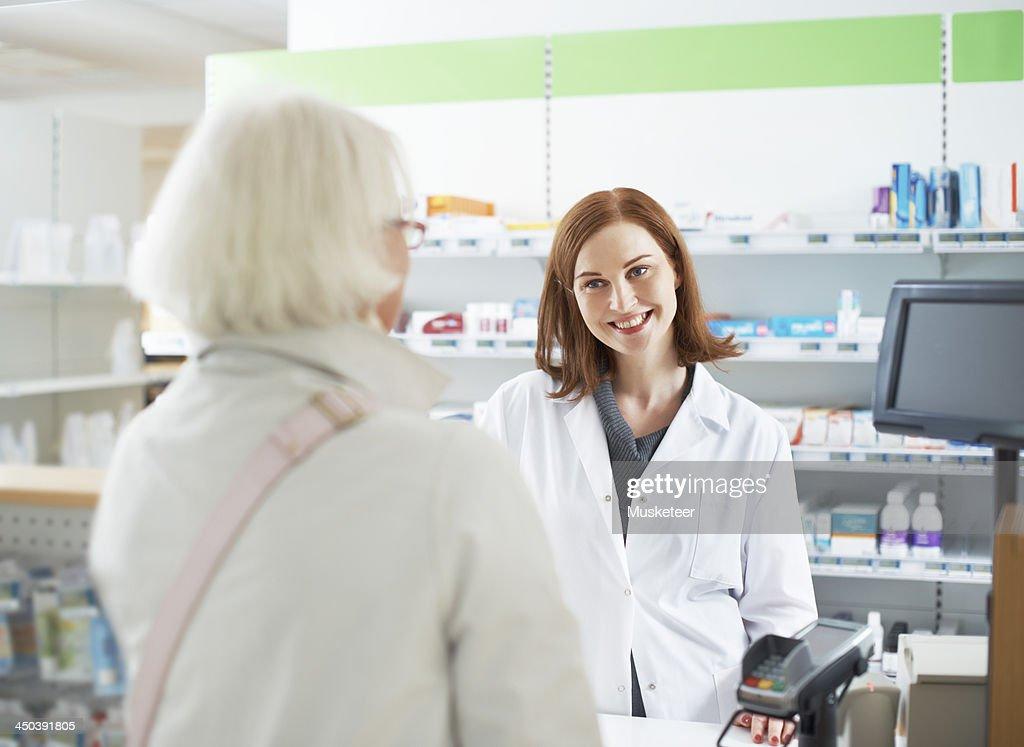 Pharmacist conversing with customer : Stock Photo