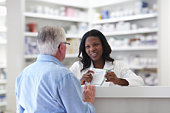Pharmacist Explaining Pamphlet To Senior